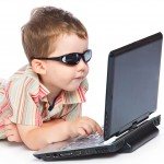 a boy in the sunglasses is typing on a laptop